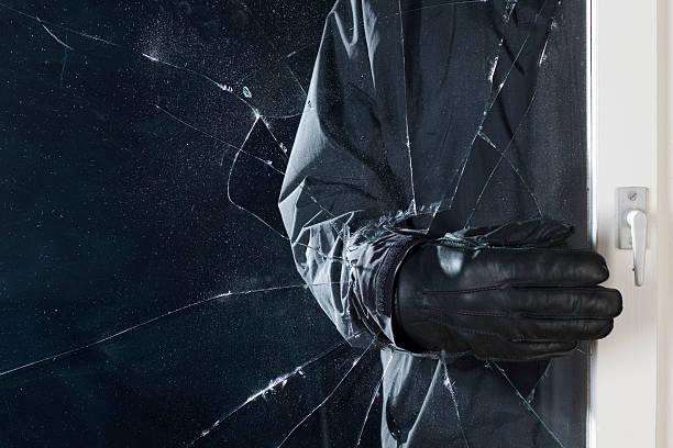 Cambrioleur qui s'introduit dans une maison par une fenêtre cassée