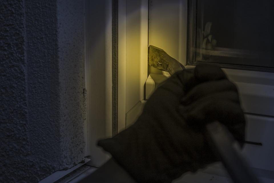 Cambrioleur qui tente de forcer une fenêtre pour s'introduire dans une maison